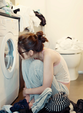 Woman staring at a washing ...